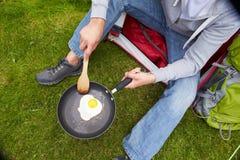 Hombre en la acampada que fríe el huevo en cacerola Fotos de archivo libres de regalías