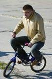 Hombre en la bici de los niños Fotografía de archivo
