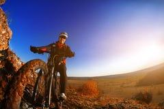 Hombre en la bici de montaña en el fondo de la puesta del sol hermosa Primer de la rueda de bicicleta Imagenes de archivo