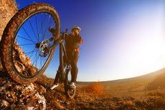 Hombre en la bici de montaña en el fondo de la puesta del sol hermosa Primer de la rueda de bicicleta Fotos de archivo