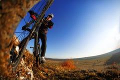 Hombre en la bici de montaña en el fondo de la puesta del sol hermosa Primer de la rueda de bicicleta Fotos de archivo libres de regalías