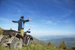 Hombre en la bici del patio de ATV en el camino de las montañas Fotografía de archivo libre de regalías