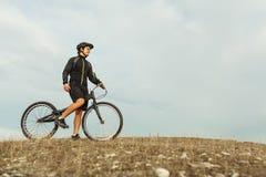 Hombre en la bicicleta que se coloca en la colina Imagenes de archivo