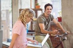 Hombre en la bicicleta usando smartphone en oficina Fotografía de archivo