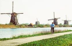 Hombre en la bicicleta y los molinoes de viento en Kinderdijk, Países Bajos foto de archivo libre de regalías
