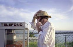 Hombre en la cabina de teléfono hispánica del lenguaje mientras que en vaca Fotos de archivo