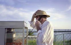 Hombre en la cabina de teléfono mientras que el vacaciones Foto de archivo libre de regalías