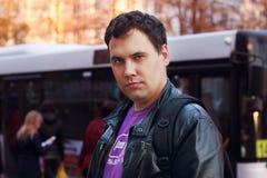 Hombre en la calle cerca de la parada de autobús en ciudad imagen de archivo