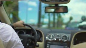 Hombre en la camisa blanca que conduce el coche costoso en la ciudad de vacaciones, transferencia del hotel de lujo metrajes