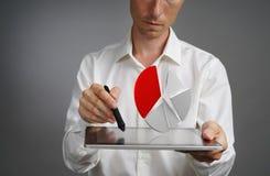 Hombre en la camisa blanca que trabaja con el gráfico de sectores en una tableta, el uso para el planeamiento del presupuesto o e Imagen de archivo libre de regalías