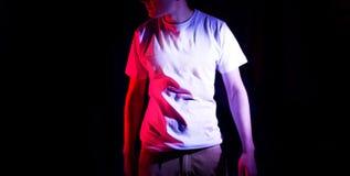 Hombre en la camiseta blanca en blanco, en un fondo negro, mofa para arriba, espacio libre con la luz roja Fotos de archivo libres de regalías
