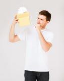 Hombre en la camiseta blanca con la caja de regalo Foto de archivo libre de regalías