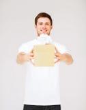 Hombre en la camiseta blanca con la caja de regalo Imagen de archivo
