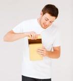 Hombre en la camiseta blanca con la caja de regalo Fotografía de archivo