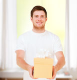 Hombre en la camiseta blanca con la caja de regalo Foto de archivo