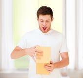Hombre en la camiseta blanca con la caja de regalo Imagen de archivo libre de regalías