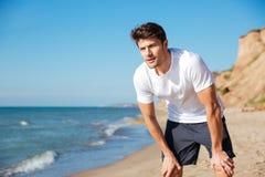 Hombre en la camiseta blanca y pantalones cortos que se colocan en la playa Imagen de archivo libre de regalías