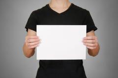 Hombre en la camiseta negra que sostiene el papel en blanco del blanco A4 Prospecto prese Fotografía de archivo libre de regalías