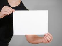 Hombre en la camiseta negra que sostiene el papel en blanco del blanco A4 Prospecto prese Foto de archivo libre de regalías