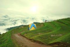 Hombre en la chaqueta anaranjada que mira la vista del paisaje de la montaña Fotografía de archivo libre de regalías