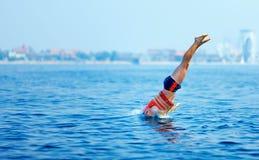 Hombre en la chaqueta del rescate que salta en agua Imagen de archivo libre de regalías