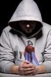 Hombre en la chaqueta encapuchada que se sienta en el vector Imagen de archivo libre de regalías