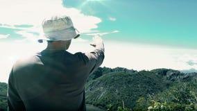Hombre en la cima de la montaña que toca el cielo metrajes