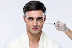 Hombre en la cirugía plástica con la jeringuilla Fotos de archivo libres de regalías