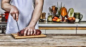 Hombre en la cocina que corta un pedazo de carne Imagenes de archivo