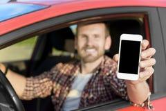 Hombre en la conducción de automóviles mostrando el teléfono elegante Foto de archivo libre de regalías