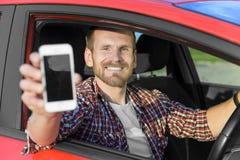 Hombre en la conducción de automóviles mostrando el teléfono elegante Fotos de archivo libres de regalías