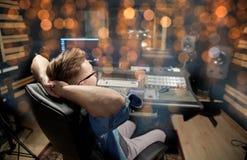 Hombre en la consola de mezcla en el estudio de grabación de la música fotografía de archivo