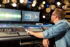 Hombre en la consola de mezcla en el estudio de grabación de la música foto de archivo libre de regalías