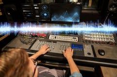 Hombre en la consola de mezcla en el estudio de grabación de la música imagen de archivo libre de regalías