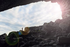 Hombre en la cueva con un fondo del cielo Fotografía de archivo