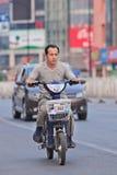 Hombre en la e-bici en el centro de ciudad de Pekín, China Fotos de archivo