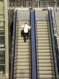 Hombre en la escalera móvil Fotografía de archivo