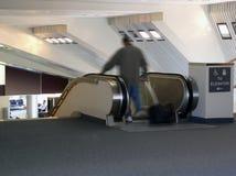 Hombre en la escalera móvil en aeropuerto Foto de archivo libre de regalías