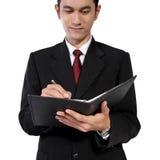 Hombre en la escritura del traje en el cuaderno, aislado en blanco Imagen de archivo