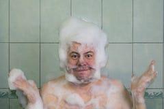 Hombre en la espuma en el cuarto de baño