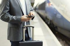 Hombre en la estación de la plataforma Mensaje de texto que mecanografía en el teléfono celular Fotos de archivo libres de regalías
