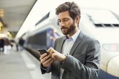 Hombre en la estación de la plataforma Mensaje de texto que mecanografía en el teléfono móvil Imágenes de archivo libres de regalías
