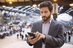 Hombre en la estación del pasillo Mensaje de texto que mecanografía en el teléfono móvil Imagenes de archivo