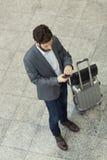 Hombre en la estación del pasillo Mensaje de texto que mecanografía en el teléfono móvil T Imagenes de archivo