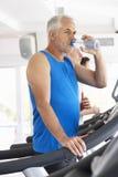 Hombre en la máquina corriente en agua potable del gimnasio Imagen de archivo libre de regalías