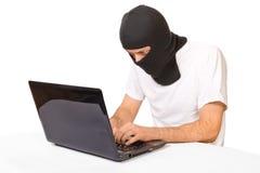 Hombre en la máscara negra que mira el monitor imagenes de archivo