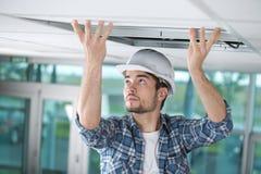 Hombre en la mano del uniforme del constructor para arriba que instala el techo suspendido fotos de archivo