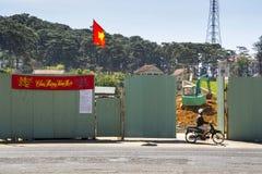 Hombre en la moto delante del emplazamiento de la obra con el excavador y bandera vietnamita el 10 de febrero de 2012 en Dalat, V Fotografía de archivo libre de regalías