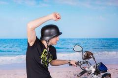 Hombre en la moto en la playa con un brazo aumentado Fotografía de archivo libre de regalías