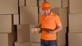 Hombre en la naranja uniforme entregando el paquete pesadamente dañado al cliente Brown encuadierna el fondo Trabajo no profesion metrajes